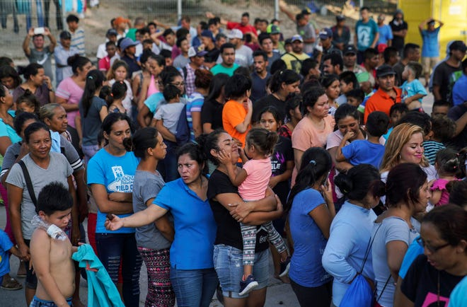 """In this Aug. 30, 2019, migrants, many who were returned to Mexico under the Trump administration's """"Remain in Mexico,"""" program wait in line to get a meal in an encampment near the Gateway International Bridge in Matamoros. In the latest twist for a signature Trump administration immigration policy, a federal appeals court said it is halting a policy next week to make asylum-seekers wait in Mexico for court hearings in the United States. But the U.S. 9th Circuit Court of Appeals in San Francisco said Wednesday, March 4, 2020, that it would only block the """"Remain in Mexico"""" policy in Arizona and California, the two border states where its authority extends."""