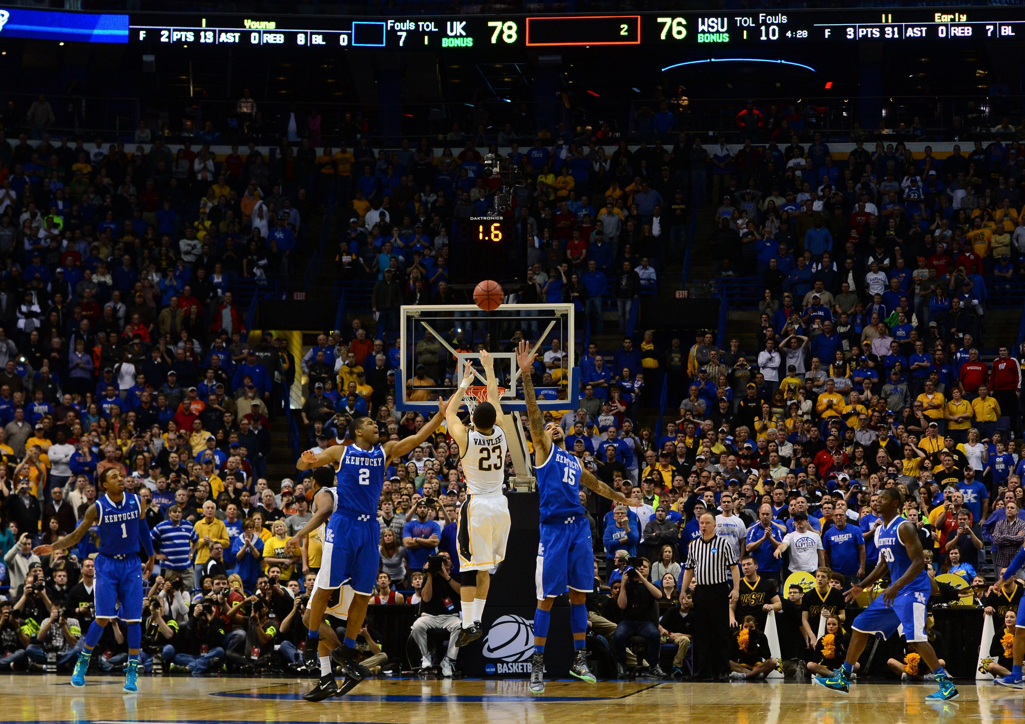 Wichita State guard Fred VanVleet takes a 3-point shot while defended by Kentucky forward Willie Cauley-Stein (15) and Aaron Harrison (2) at the 2014 NCAA Tournament.