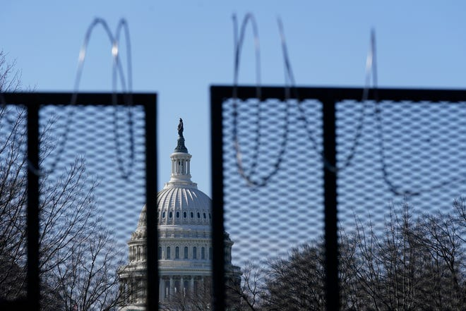 FILE - In this March 20, 2021, file photo the U.S. Capitol dome stands past partially-removed razor wire hanging from a security fence on Capitol Hill in Washington. Authorities suggested for weeks in court hearings and papers that members of the Oath Keepers militia group planned their attack on the Capitol in advance in an effort to block the peaceful transition of power. But prosecutors have since said it's not clear whether the group was targeting the Capitol before Jan. 6, giving defense attorneys an opening to try to sow doubt in the government's case. (AP Photo/Patrick Semansky, File) ORG XMIT: WX106