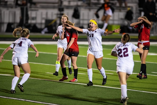 Round Rock's Jordan Doss, center, celebrates after Kara Harris, left, scored the only goal of the match in overtime of a Class 6A regional quarterfinal Friday against Lake Travis.