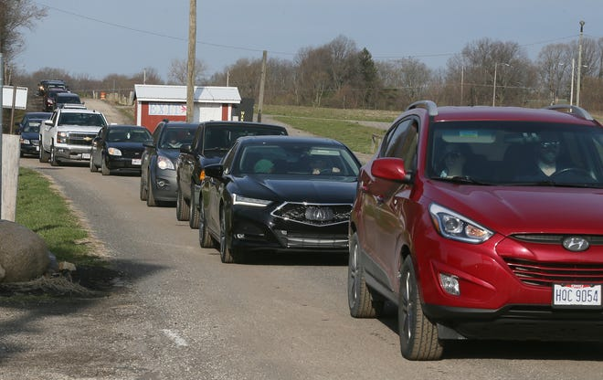 Cars line up to get into the Summit County Public Health COVID-19 mass vaccination site at the Summit County Fairgrounds April 3 in Tallmadge. The clinic used the Johnson & Johnson vaccine before its use was paused.