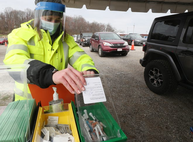 Leah Webb, a nurse at Summit County Public Health, gets the supplies to administer a shot at the COVID-19 mass vaccination site at the Summit County Fairgrounds April 3 in Tallmadge. The health department is resuming using the Johnson & Johnson vaccine after its use was paused due to a rare blood-clotting disorder.