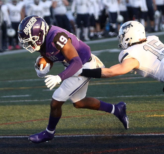 Mount Union wide receiver Jaden Manley, left, crosses the goal line for a first-quarter touchdown defended by Marietta's Darius Hatch (15) following a catch during their game at Mount Union Stadium on Friday, April 2, 2021.