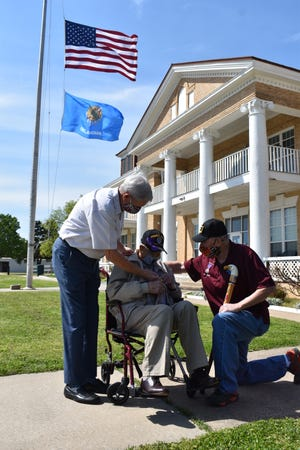 Joe Bartlett, center, holds his Purple Heart for the first time Friday, April 2, 2021, outside the Oklahoma Veterans Center in Ardmore. He was injured in June 1945 when Japanese kamikaze pilot attacked his Navy ship in the Pacific about two months before the end of World War II.