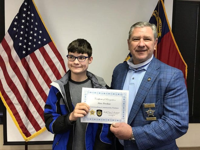 Alex Perdue stands with Randolph County Sheriff Greg Seabolt as he accepts a certificate for reporting road conditions to the Department of Transportation.