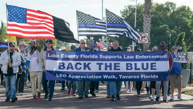 People march down Ruby Street at a Back the Blue rally in downtown Tavares on Saturday, April 3, 2021. [PAUL RYAN / CORRESPONDENT]