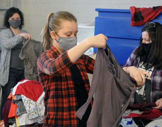 """Anderson """"Andi"""" Musser, a fifth-grader at Shreve Elementary, sorts through gently used clothing at Goodwill in Wooster. She'll use the donated items to stock the Kindness Closet at school."""