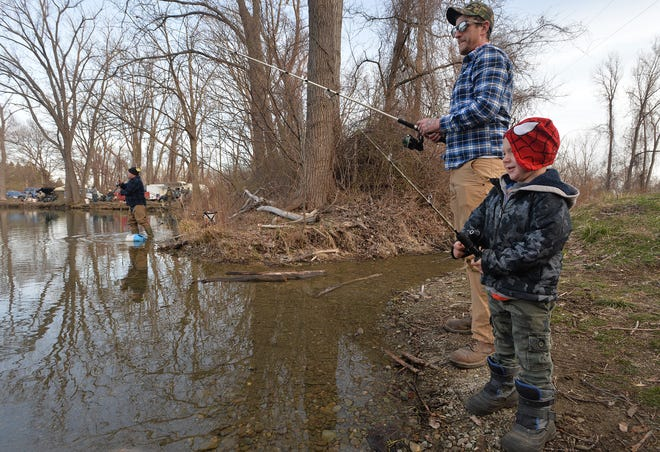 Mike Ferguson, 32, fishes with his stepson Bentley Holfelder, 5, on Saturday, opening day of Pennsylvania trout season, at the Fairview Gravel Pit pond in Fairview Township.