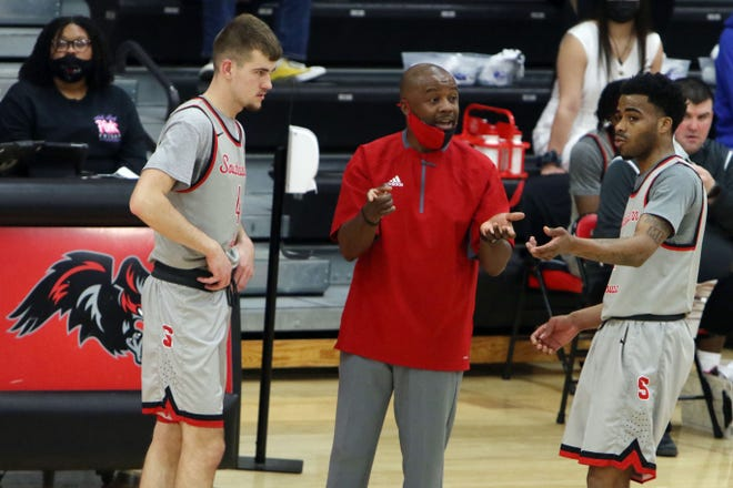 Southeastern Community College's head coach Lorenzo Watkins talks with Gavin Kies (4) and Kennedy Milton (2) during their Region XI Tournament semifinal game against Marshalltown Community College Saturday April 3, 2021, at SCC's Loren Walker Arena.