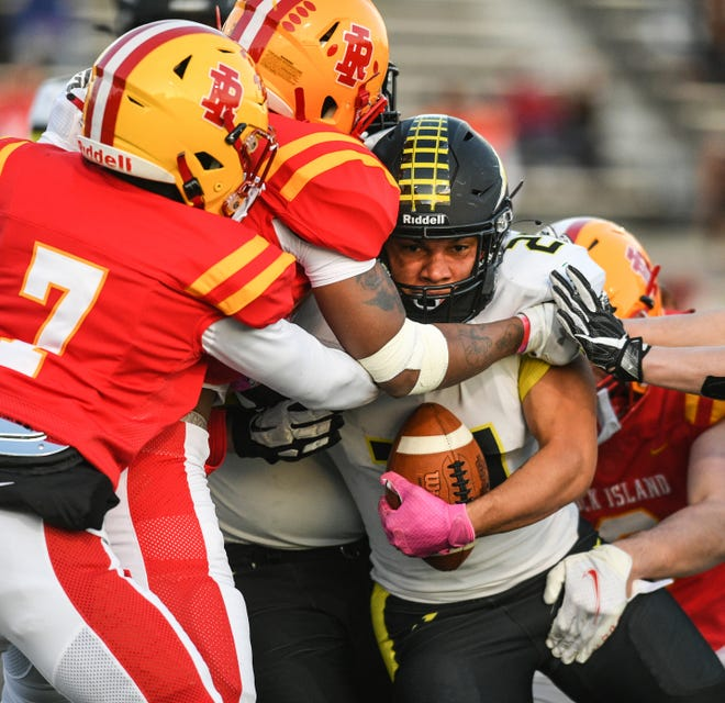 Galesburg's Kyron Leath (21) is brought down by a group of Rock Island defenders during their game at Almquist Field on Friday, April 2, 2021, in Rock Island.