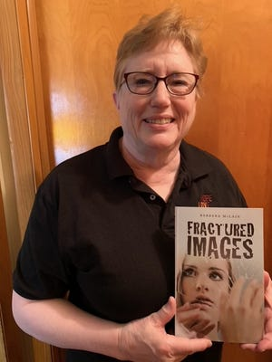 Ransom author Barbara McLain holds a copy of her new book, Fractured Images.