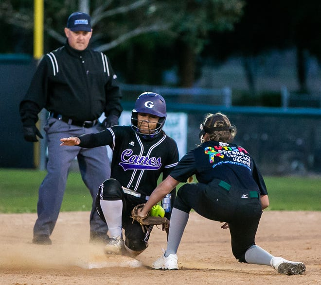 Gainesville's Ayanna Woodard beats the throw to second in the top of the fourth as Forest's Savannah Nolin gets the ball late. The Hurricanes defeated the Wildcats, 15-5, Friday night.