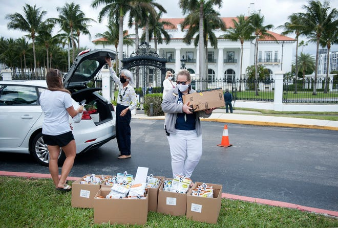 Aleese Kopf, of the Town of Palm Beach United Way, left, and Flagler's Spirit team member Allison Goff collect donations from Vivian Chen Saturday at The Flagler Museum during the annual Empty Your Pantry Food Drive.