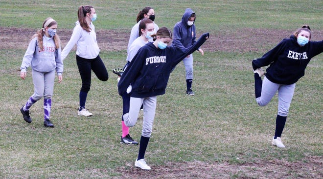 Members of the Exeter High School softball team stretch before Thursday's practice. In total, 48 girls came out for the team this season.