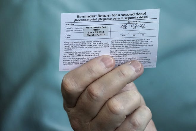 Juan Carlos Guerrero, 62, holds his second-shot reminder card as he speaks to a health care worker after receiving a dose of the Pfizer COVID-19 vaccine last month at the Miami-Dade County Tropical Park vaccination site in Miami. WILFREDO LEE / ASSOCIATED PRESS