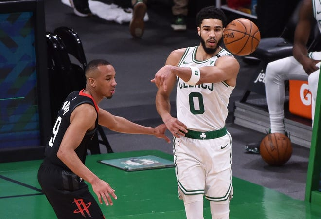 Celtics forward Jayson Tatum dishes the ball past Rockets guard Avery Bradley on Friday night in Boston's 118-112 win.