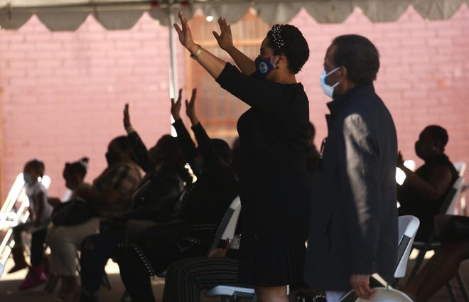 Parishioners of Mt. Moriah Church LA worship during a socially distanced outdoor Sunday service under big tents in the church parking lot in Los Angeles on Nov. 29, 2020. For many churches, hope for returning to churches has come in the form of COVID-19 vaccines as more and more inoculated members are slowly leading to a return to pre-pandemic worship.