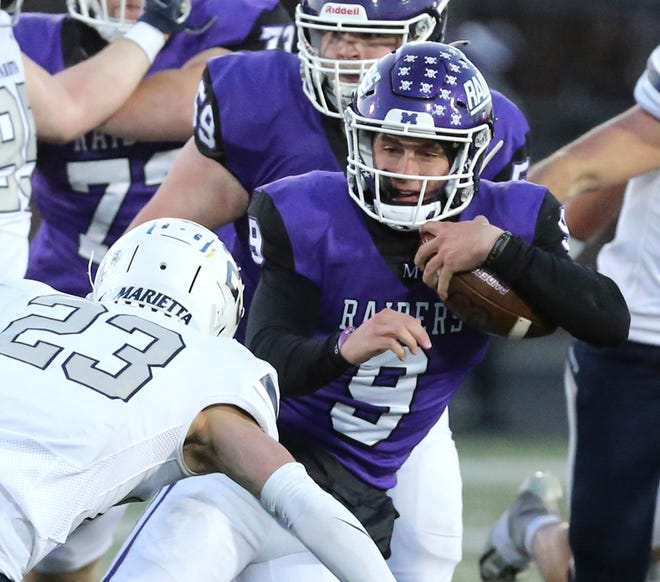 Mount Union quarterback Braxton Plunk (9) picks up yardage before being taken down by Marietta's Kyler Folkert (23) during Friday's game.