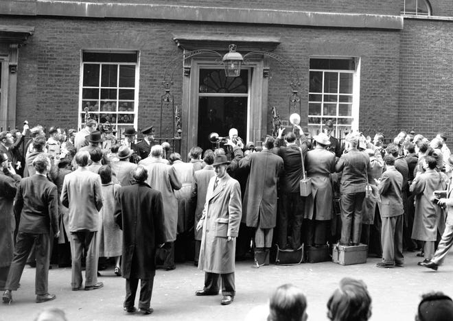 Britain's Prime Minister Sir Winston Churchill, in doorway, center, smoking cigar, leaves No. 10 Downing Street, London, to tender his resignation to Queen Elizabeth II on April 5, 1955. Churchill is faced by a solid crowd of press photographers.