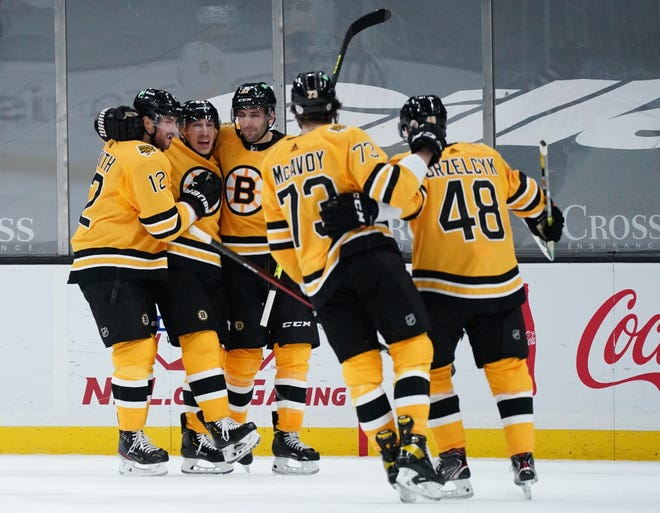 Bruins center Brad Marchand, second from left, is congratulated after his goal against the Penguins during Saturday's second period at TD Garden.