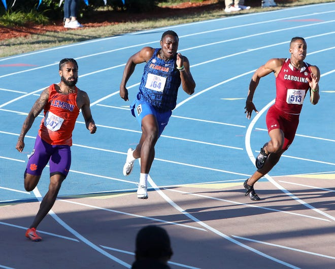 Joseph Fahnbulleh, center, a Florida Gators sprinter, runs in the men's 200m race where he would finish with a personal best 20.10 and win the race Friday during the 2021 Pepsi Florida Relays at Percy Beard Track at the Florida campus.