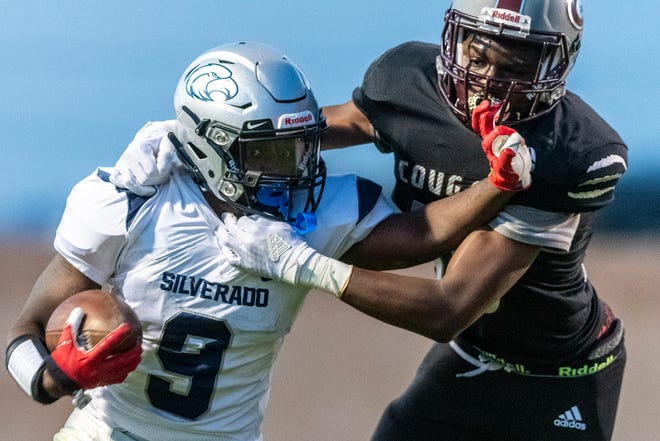 Silverado's Jawan Howard stiff arms a Granite Hills defender during the second quarter on Friday, April 2 2021. Howard scored six touchdowns against the Cougars.