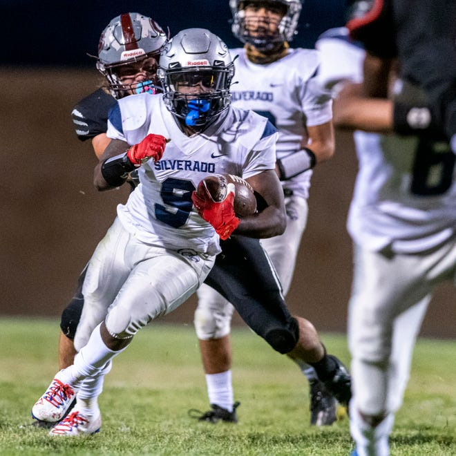 Silverado's Jawan Howard, center, carries the ball upfield against Granite Hills on Friday, April 2, 2021. Howard scored six touchdowns in the 44-24 victory over the Cougars.