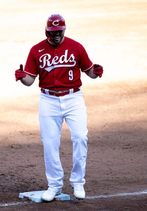 Cincinnati Reds second baseman Mike Moustakas (9) celebrates after hitting an RBI base hit in the third inning of the MLB baseball game between Cincinnati Reds and St. Louis Cardinals at Great American Ball Park in Cincinnati on Saturday, April 3, 2021.
