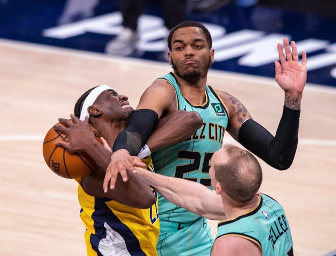 Indiana Pacers guard Caris LeVert (22) is fouled by Charlotte Hornets forward P.J. Washington (25) while taking a shot during the second half of an NBA basketball game in Indianapolis, Friday, April 2, 2021. (AP Photo/Doug McSchooler)