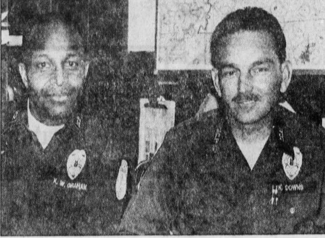 Officer Kenny Downs (right) was with pilot Kenny Graham (seated with him) when they saw the UFO. They described it as a glowing pear-shaped object about the size of a basketball that at one point shot three baseball-size fireballs out of its middle.