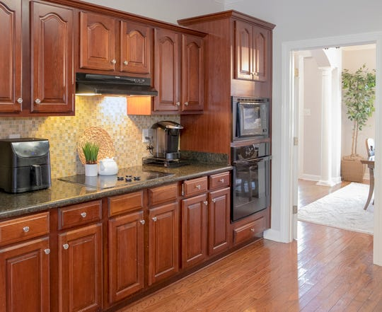 The kitchen has a wall of cabinets providing an abundance of storage.