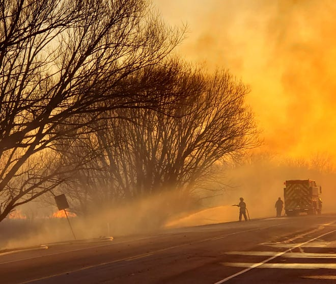 A firefighter battles a wildfire on Good Hope Road, west of Pilgrim Road, in Menomonee Falls on Friday, April 2.