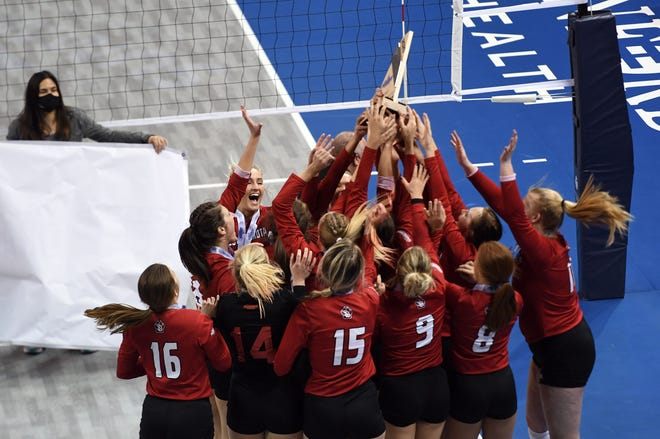The South Dakota volleyball team holds their trophy aloft after winning the Summit League championship on Saturday, April 3, 2021, at the Sanford Pentagon in Sioux Falls.