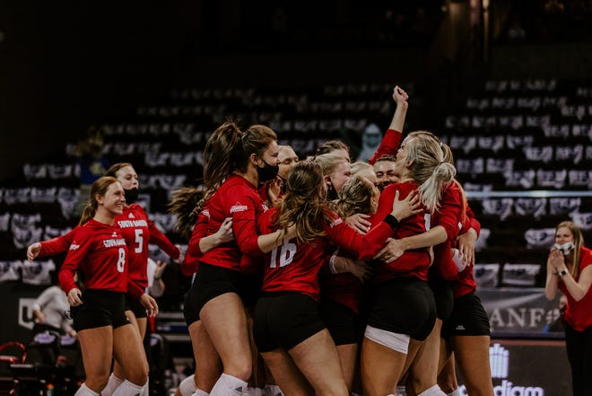 The South Dakota volleyball team celebrates following its 3-2 victory over Kansas City in the Summit League semifinals.