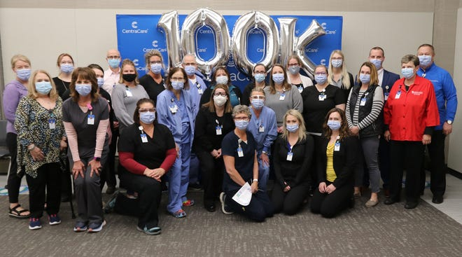 CentraCare CEO and President Dr. Ken Holmen, members of the COVID-19 Incident Command team and leaders of the vaccine team take a photo to commemorate giving the 100,000th dose.