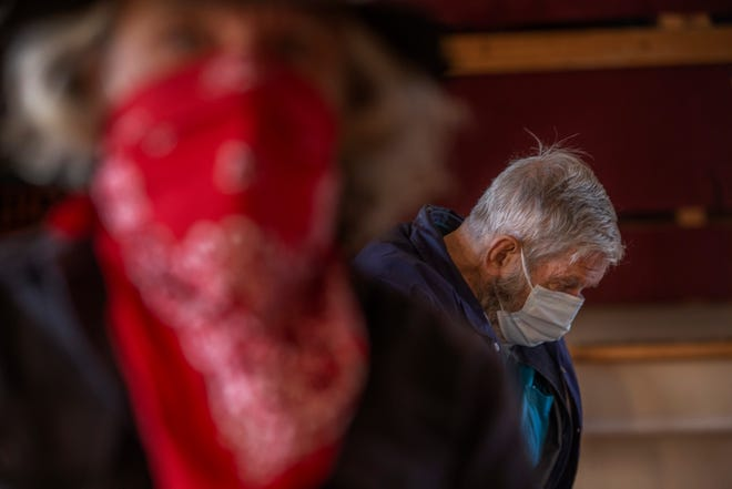 Randall Streier, at back, and Jim Laupan, sit in an observation area after receiving their COVID-19 vaccination from the New Mexico Department of Health at the Hillsboro Community Center during the rural community's first COVID-19 vaccination distribution.