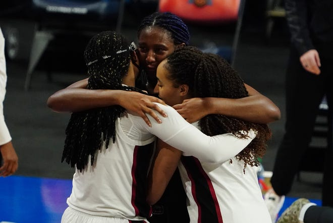 Cardinal guard Haley Jones (right) and forward Francesca Belibi hug Gamecocks forward Aliyah Boston after Boston missed a last-second shot that would have won the game for South Carolina.