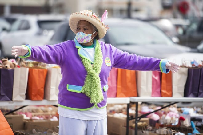 Valerie McElvy directs traffic as 970 Easter bags are handed out by the  borough of New Brighton at a drive-through Easter bag give-away Saturday on Fourth Street.