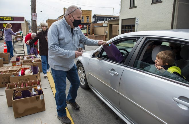 Robb Hartwick hands out bags of Easter treats during a drive-through Easter bag give-away Saturday by New Brighton borough.