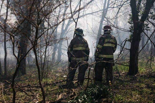 Bartlesville firefighters Michael Kramer and David Neer protect homes in the 1800 block of Elm from a brush fire on Easter as strong winds from the south feed the flames.
