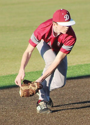 A Dewey High infielder scoops up the ball and prepares to make a play during action in March.