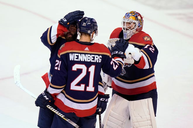 Alex Wennberg (21) is congratulated by Sergei Bobrovsky (72) and defenseman Radko Gudas, left, after Wennberg notched his first career hat trick with a long empty-net goal with 6.9 seconds left in the Florida Panthers' 5-2 victory against the Blue Jackets on Saturday night in Sunrise, Fla.