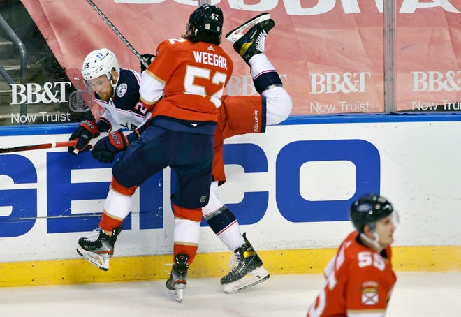 Mikhail Grigorenko (25) gets smashed by Florida Panthers defenseman MacKenzie Weegar (52) during the first period Sunday at BB&T Center in Sunrise, Fla.