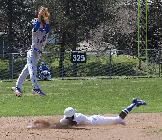 Cambridge senior Sean Perkins slides safely into second base as Maysville's Tyler Jason (14) goes up high to catch the baseball during Saturday's doubleheader at Don Coss Field.