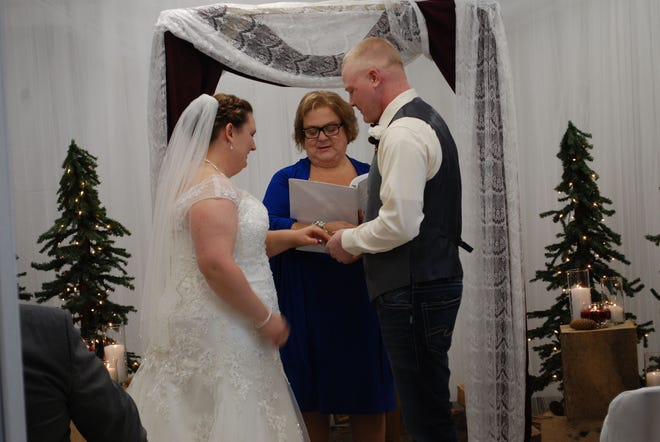 Hudson Mayor Carmel Camp admits she has trouble saying no to performing wedding ceremonies — she's done 31 one of them. Camp is pictured with Kayla and Trevor Francoeur.
