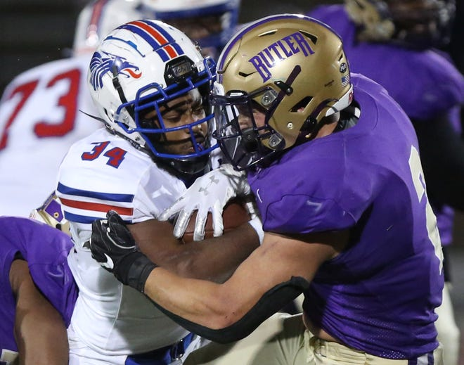 Hutchinson's Ronald Hoff (34) is stopped by Butler's Hunter Lee (2) during their game Saturday night in El Dorado. Hutchinson defeated Butler 41-10.