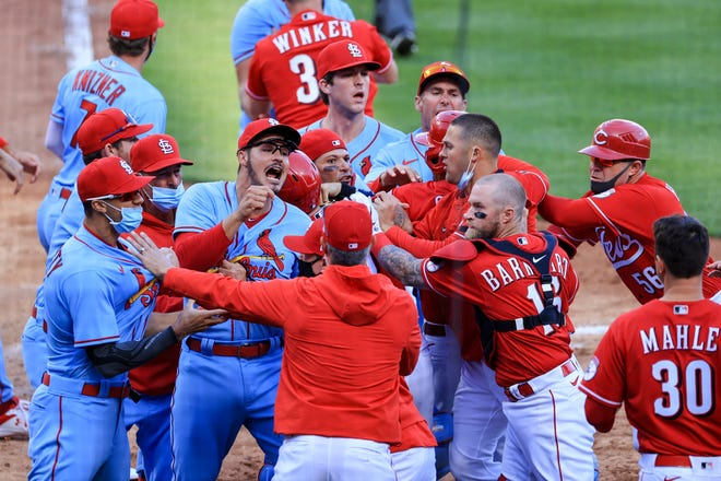 St. Louis Cardinals' Nolan Arenado, center left, reacts alongside teammate catcher Yadier Molina, center, as they scrum with members of the Cincinnati Reds during the fourth inning of a baseball game in Cincinnati, Saturday, April 3, 2021.