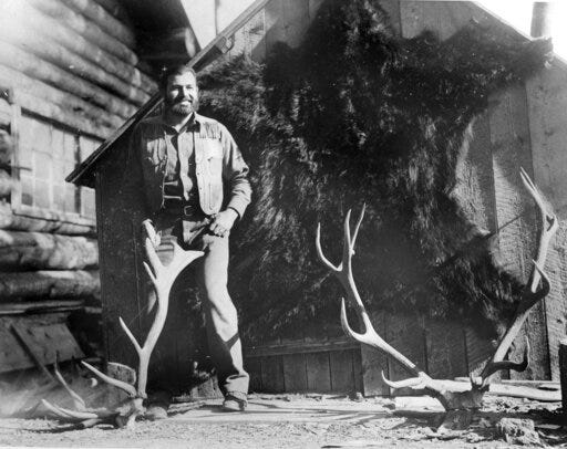 In this 1932 photo provided by the John F. Kennedy Library Foundation from the Ernest Hemingway Collection Ernest Hemingway posing with a bear skin and deer antlers during a hunting trip to Nordquist's Ranch in Wyoming. A new three-part documentary about Hemingway, which relied heavily on the archives at the John F. Kennedy Presidential Library and Museum in Boston, debuts Monday on PBS