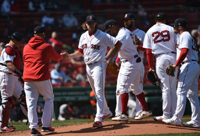 Red Sox manager Alex Cora takes the ball from starting pitcher Garrett Richards during the third inning of Sunday's game against the Baltimore Orioles. Richards gave up seven hits and six runs in only two innings as Boston lost its third straight game.