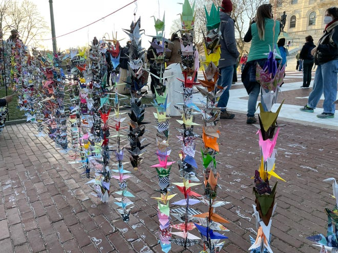 Origami cranes are displayed at the State House lawn on Saturday as part of an event protesting violence and abuse targeting the Asian community in the wake of the COVID pandemic.
